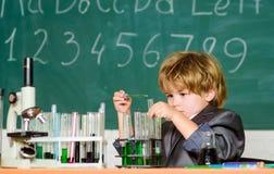 Microscópio do menino e sala de aula da escola dos tubos de ensaio Conceito do conhecimento Assunto fascinante Dia do conheciment imagem de stock