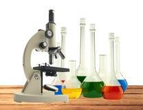 Microscópio e tubos de ensaio do metal do laboratório com líquido em de madeira imagens de stock royalty free