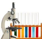 Microscópio e tubos de ensaio do metal do laboratório com o líquido isolado Foto de Stock