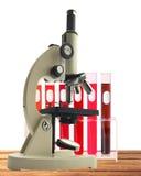 Microscópio e tubos de ensaio do metal do laboratório com sangue no suporte Imagens de Stock