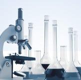 Microscópio e tubos de ensaio do metal do laboratório com tonificação líquida Fotografia de Stock Royalty Free