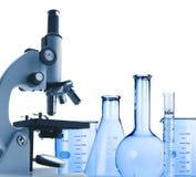 Microscópio e tubos de ensaio do metal do laboratório isolados no branco Foto de Stock Royalty Free