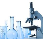 Microscópio e tubos de ensaio do metal do laboratório isolados no branco Fotos de Stock