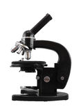 Microscópio preto velho dos objetivos do clássico quatro isolado em um fundo branco Fotos de Stock Royalty Free