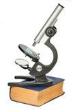 Microscópio que está no livro velho grosso isolado no branco Foto de Stock Royalty Free