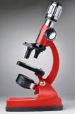 Microscópio vermelho no cinza Foto de Stock Royalty Free