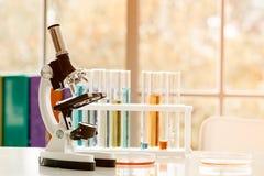 Microscoop op lijst met laboratoriummateriaal in chemisch laboratorium met lichte gloed stock foto