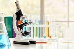 Microscoop op lijst met laboratoriummateriaal in chemisch laboratorium met lichte gloed royalty-vrije stock fotografie