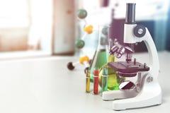 Microscope avec la verrerie de laboratoire, les flacons et les colbas Laborat de la Science Photo stock