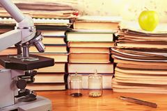 Microscope and books in scientific study Royalty Free Stock Photos