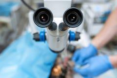 Microscope chirurgical d'ophtalmologue de v?t?rinaire dans la salle d'op?ration et le chien avec l'oeil bless? sur la table de fo image libre de droits