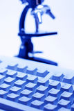 Microscope and Computer Keyboard Royalty Free Stock Photography