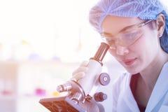 Microscope de throgh de regard de scientifique image stock