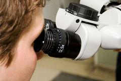 Microscope II. Young doctor looking into the microscope Royalty Free Stock Photo