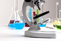 Microscope and laboratory flacks Royalty Free Stock Images