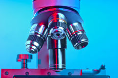 Microscope lenses lit in red and blue Royalty Free Stock Image