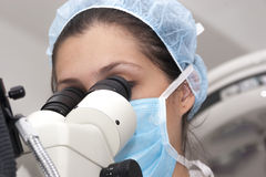 At the microscope. Medical  professional looking through a microscope Stock Images