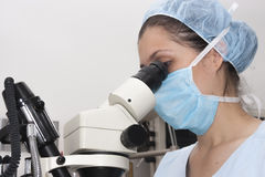 At the microscope. Medical  professional looking through a microscope Stock Photo