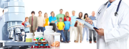 Microscope pills and people group. Royalty Free Stock Photo
