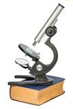 Microscope standing on the thick old book isolated on white Royalty Free Stock Photo