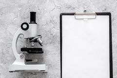 Microscope and tablet on grey stone background top view mockup Royalty Free Stock Images