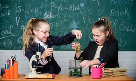 Microscope and test tubes on table. Educational experiment concept. Be careful performing chemical reaction. Basic. Knowledge of chemistry. Girls study stock photos