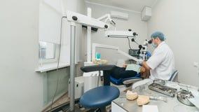 Microscope utilisé par docteur Le dentiste soigne le patient dans le bureau dentaire moderne L'opération est effectuée utilisant  images libres de droits