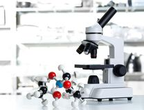 Microscopio con el modelo de la molécula en laboratorio Imagen de archivo libre de regalías