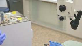 Microscopio utilizzato medico Il dentista sta curando il paziente in ufficio dentario moderno Lavoro dell'ortodontista con l'assi video d archivio