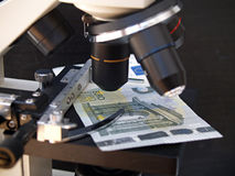 Microscopio y dinero Fotografía de archivo libre de regalías