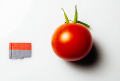 MicroSD card next to cherry tomato Stock Photo