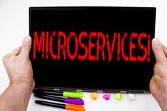 Microservices text som är skriftlig på minnestavlan, dator i kontoret med markören, penna, brevpapper Affärsidéen för Micro serva Royaltyfri Bild