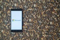 Microsoft-Logo auf Smartphone auf Hintergrund von kleinen Steinen Stockfotografie