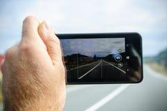 Microsoft lumiatelefon i handen som tar fotoet av huvudvägen Arkivfoto