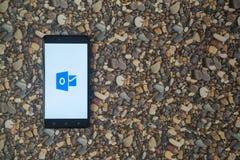 Microsoft Office-Aussichtlogo auf Smartphone auf Hintergrund von kleinen Steinen Lizenzfreie Stockbilder