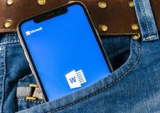 Microsoft słowa podaniowa ikona na Jabłczany X iPhone parawanowym zakończeniu w cajgach wkładać do kieszeni Microsoft Office słow fotografia royalty free