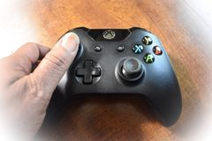Hand Holding An Xbox One Wireless Controller On A Wood Table, Editorial. Microsoft Xbox One is a top gaming console brand. This photo displays the look of the Royalty Free Stock Photography