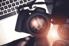 Microstock Photo Business. Concept Photo with Digital Camera and Dollar Banknotes Reflection Inside the Lens and Laptop Computer. Making Money Taking Pictures Stock Photo