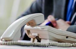 Microteléfono blanco y un teléfono en el escritorio en oficina Imagen de archivo libre de regalías