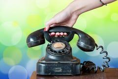 Microteléfono colgante de la mano de la mujer Foto de archivo libre de regalías