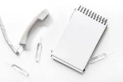 Microteléfono del teléfono con el cuaderno en la composición blanca de la opinión superior del fondo con mofa del doctor de la ll Fotos de archivo libres de regalías