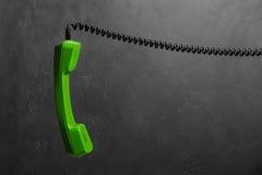Microtelefono dal telefono della linea terrestre sulla parete del fondo fotografia stock