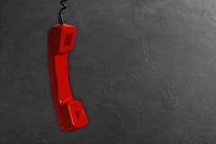 Microtelefono dal telefono rosso della linea terrestre su un fondo grigio della parete immagini stock