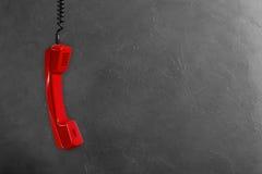 Microtelefono dal telefono rosso della linea terrestre su un fondo grigio della parete fotografie stock