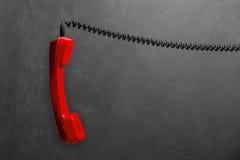 Microtelefono dal telefono rosso della linea terrestre su un fondo grigio della parete immagini stock libere da diritti