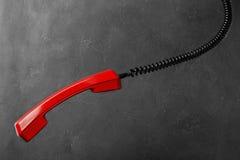 Microtelefono dal telefono rosso della linea terrestre su un fondo grigio della parete fotografia stock libera da diritti