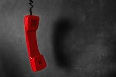 Microtelefono dal telefono rosso della linea terrestre su un fondo grigio della parete immagine stock libera da diritti
