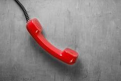 Microtelefono dal telefono rosso della linea terrestre sulla parete del fondo fotografia stock