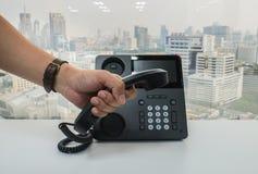 Microtelefono del telefono del IP della tenuta dell'uomo d'affari da richiedere la riunione di conferenza fotografie stock