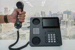Microtelefono del telefono del IP della tenuta dell'uomo d'affari da richiedere la riunione di conferenza fotografia stock